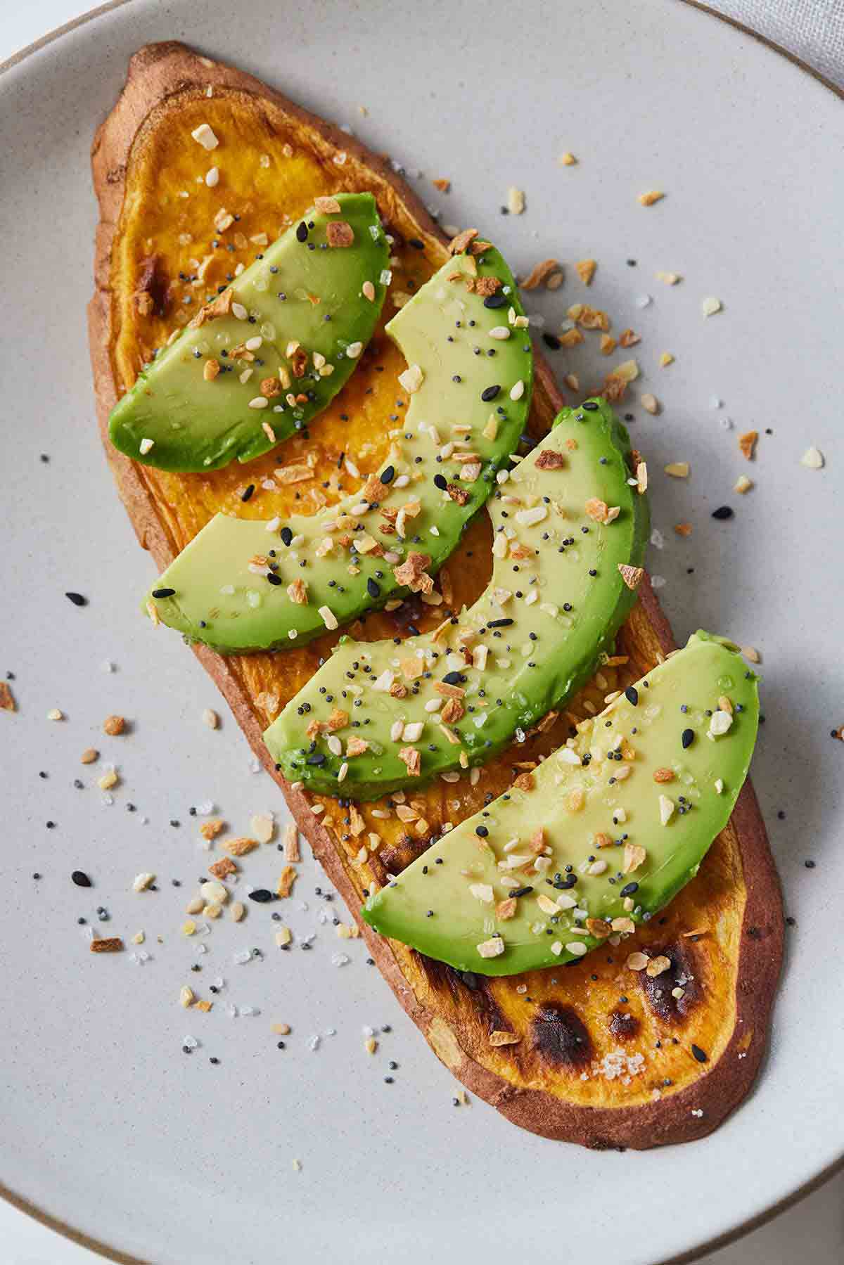 Overhead view of a sweet potato toast with sliced avocado on top.