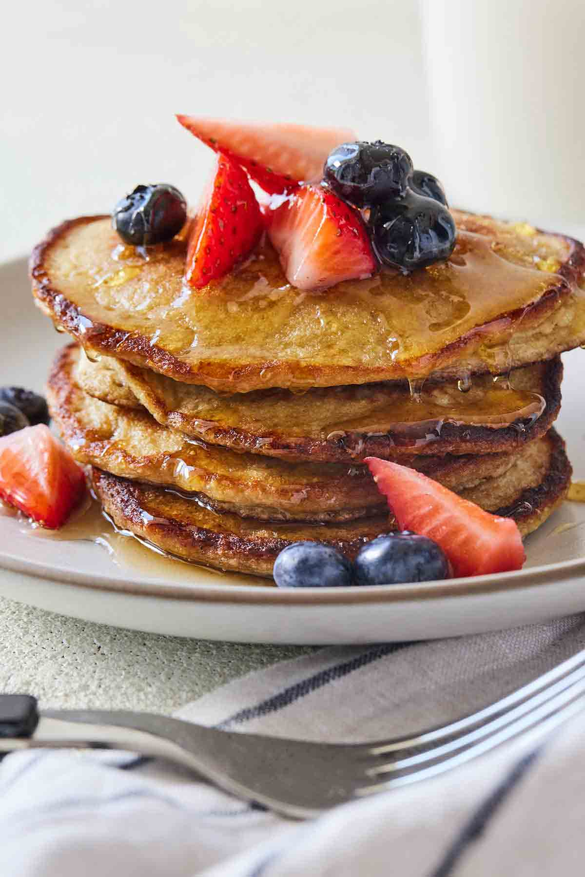 A stack of multiple banana oatmeal pancakes with fruit on top.