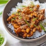 Pinterest graphic of a bowl of rice topped with cashew chicken and sliced green onions and sesame seeds.
