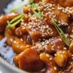 Pinterest graphic of a close up of cashew chicken with sesame seeds and sliced green onions.