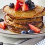 Pinterest graphic of a plate of oatmeal banana pancakes with strawberries and blueberries on top.