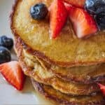 Pinterest graphic of a stack of oatmeal banana pancakes and strawberries and blueberries on top.