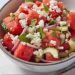 Pinterest graphic of a bowl of watermelon salad with cucumbers, onions, feta, and mint.